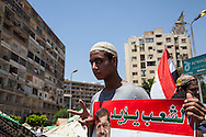 """A young man holds a poster that reads """"the people want"""" with a photo of arrested president Morsi."""