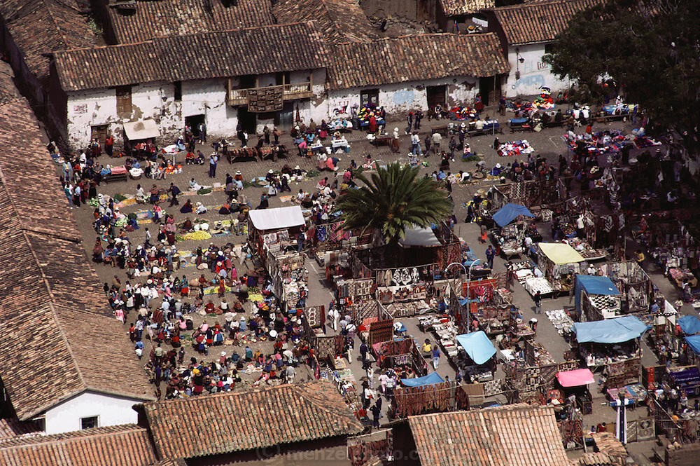 Pisac, Peru, seen from the Inca ruins on the hill overlooking the town in the Urubamba Valley, the Sacred Valley of Incas. Sunday market is in full swing in central plaza of the town. Telephoto view of plaza with colorful market.