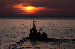 © Licensed to London News Pictures. <br /> 05/05/2016. <br /> Staithes, UK.  <br /> <br /> A fishing boat leaves the harbour to check lobster and crab pots as the sun rises in the small North Yorkshire fishing village of Staithes.<br />   <br /> Photo credit: Ian Forsyth/LNP