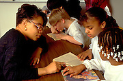 Inner city kids and teacher age 10 and 25 reading in after school program.  St Paul  Minnesota USA