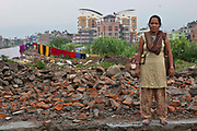A Nepalese woman stands in front of her recently demolished home in United Nations Park, Paurakhi Basti, next to the Bagmati River in the centre of Kathmandu, Nepal.  Her home was an illegal shack made from bricks, wood and plastic.  The government forces arrived in the middle of the night and used tear gas to displace the residents before demolishing their homes.  She as returned to try to rescue a few of her possessions.  Behind the slum wealthy apartment blocks have been developed.
