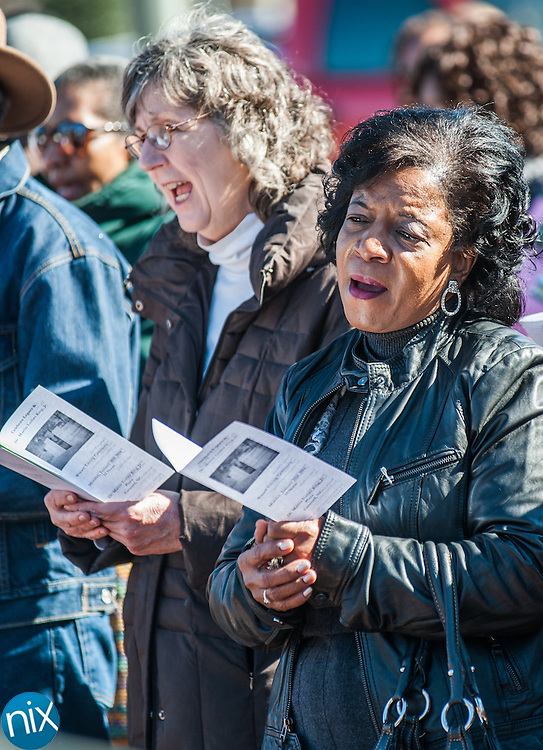 Participants sing during a wreath laying ceremony honoring the legacy of Dr. Martin Luther King Jr. at the MLK Plaza in Concord Monday afternoon.