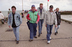 Group of men with learning disabilities walking along seaside pier with volunteer support workers,