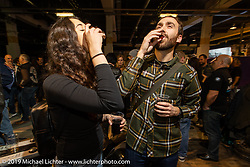 Jeni and Sean enjoying a must at the Rokker Apparel booth, their official drink Appenzeller, at their Friday night party during the Swiss-Moto Customizing and Tuning Show. Zurich, Switzerland. Friday, February 22, 2019. Photography ©2019 Michael Lichter.