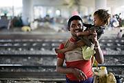 Patti Das and his child Khrisha on a piece of waste ground beneath a flyover near Okhla station. New Delhi, India.