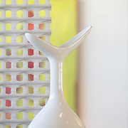 Modern, white vase against out of focus interior background