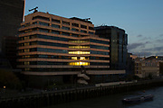 Sunset reflection in the windows of offices at St Magnus House on the River Thames in London, England, United Kingdom.