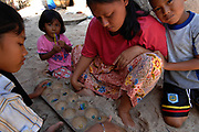 Family playing marble game, Songkhla, Thailand