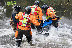 Denham, UK. 8th December, 2020. Hampshire Police officers remove an anti-HS2 activist from the river Colne for arrest during a large security operation to extract Dan Hooper, widely known as Swampy in the 1990s, from a bamboo tripod which he had occupied the previous day in order to delay the building of a bridge as part of works for the controversial HS2 high-speed rail link.