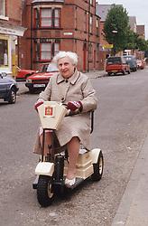 Elderly woman riding motorised scooter down street,