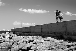 Una coppia passeggia sul frangiflutti che delimita ad ovest il porto di Gallipoli (LE)