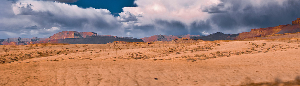 Storm clouds drop rain in the distance in rugged mesa and canyon lands of Central Utah near Green River