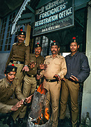 Policemen outside Foreigner's Registration Office warm themselves on a winter's morning, Darjeeling, India
