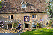 Cyclists cycling past typical English pub The Victoria in the village of Eastleach Martin in The Cotswolds, UK