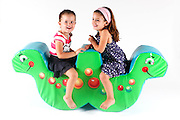 Indoor playground 2 young girls on a seesaw On white Background