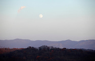Salisbury Mills, New York - An almost full moon rises above the Hudson Highlands, in the background, on Nov. 20, 2010.