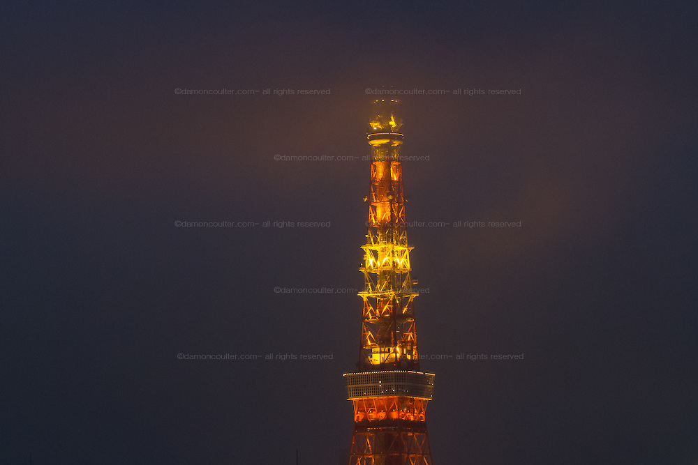 Tokyo Tower illuminated at night in bad weather and low cloud. Roppongi, Tokyo, Japan Friday October 28th 2016