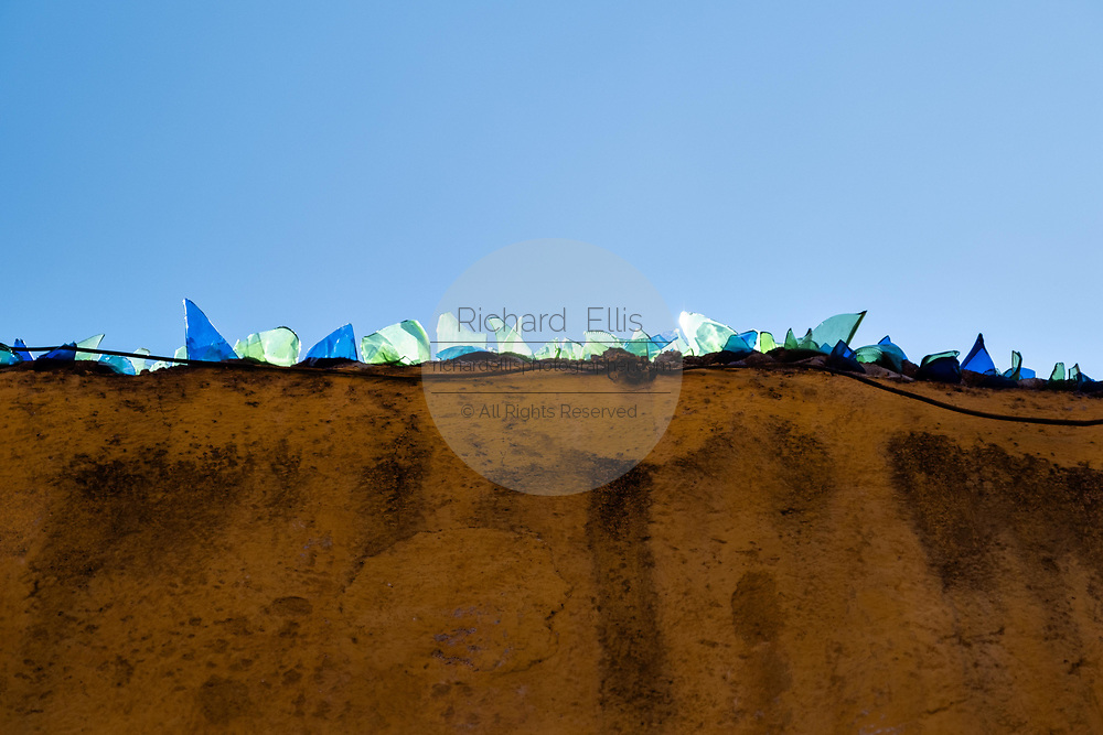 Colorful glass shards on an adobe wall as crude security against burglars glow against a clear blue sky in the historic center of San Miguel de Allende, Guanajuato, Mexico.