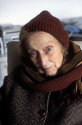 Portrait of elderly woman wearing winter clothes; looking startled,