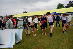 © Licensed to London News Pictures. 28/06/2017. London, UK. Spectators duck underneath a boat as it is carried form the water on day one of the Henley Royal Regatta, set on the River Thames by the town of Henley-on-Thames in England.  Established in 1839, the five day international rowing event, raced over a course of 2,112 meters (1 mile 550 yards), is considered an important part of the English social season. Photo credit: Ben Cawthra/LNP