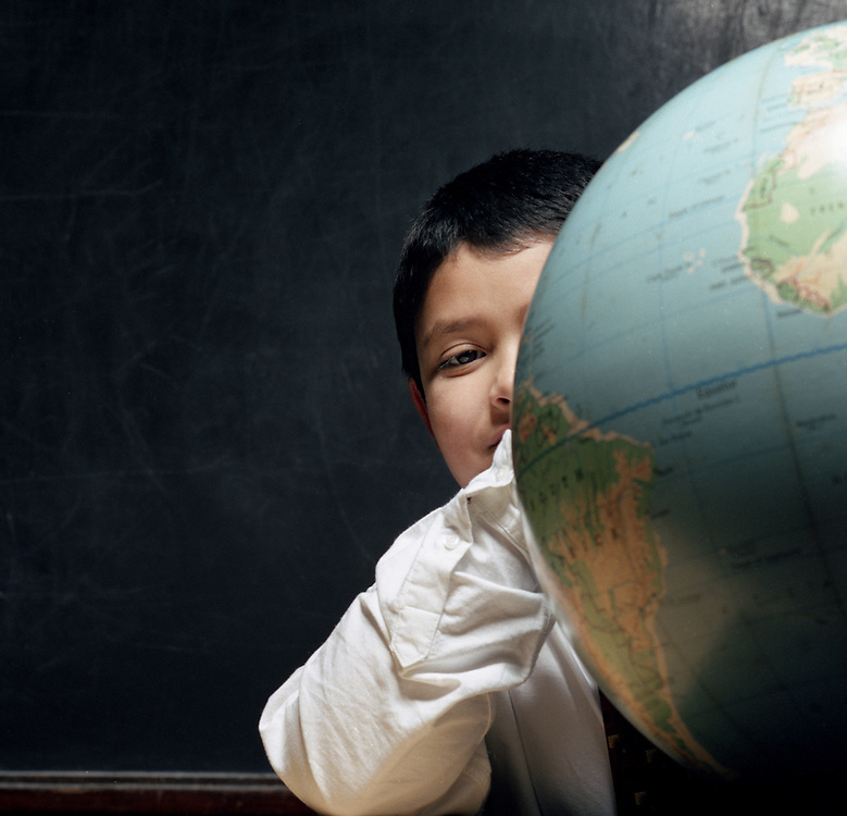 Young boy looking at camera next to globe in classroom