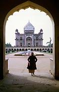 Woman walking through archway towards Safdarjung Tomb built 1754, Mughal architecture, Safdarjung ka Maqbara, New Delhi, India in 1964
