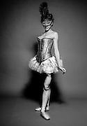 Female dancer with carnival mask on black background