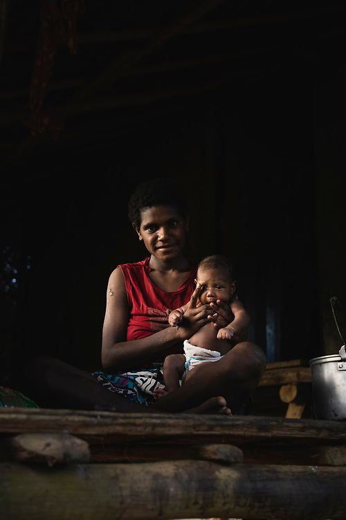 Ageles Sopam, illuminated by light from the setting sun, holds her baby inside their home in Likan, East Sepik Province, Papua New Guinea.<br /> <br /> (June 20, 2019)
