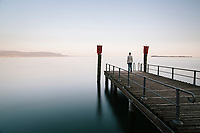 GARDONE RIVIERA, ITALY - 19 APRIL 2018: A man stands on the  pier of the Grand Hotel Fasano at dusk in Gardone Riviera, Italy, on April 19th 2018.<br /> <br /> Lake Garda is the largest lake in Italy. It is a popular holiday location located in northern Italy, about halfway between Brescia and Verona, and between Venice and Milan on the edge of the Dolomites. The lake and its shoreline are divided between the provinces of Verona (to the south-east), Brescia (south-west), and Trentino (north).