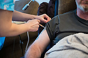 A patient receiving the COVID-19 vaccination as part of a home visiting service for housebound patients from Dr Fordham of the Channel Health Alliance at their home in the community outside Dover to administer the COVID-19 Vaccination on the 27th of February 2021, Dover, Kent, United Kingdom.