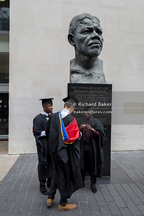 Young graduates stand beneath the bust of Nelson Mandela after their graduation eremony, in celebration of their university academic achievement, outside the Festival Hall, on 20th July 2017, on the Southbank, London, England.