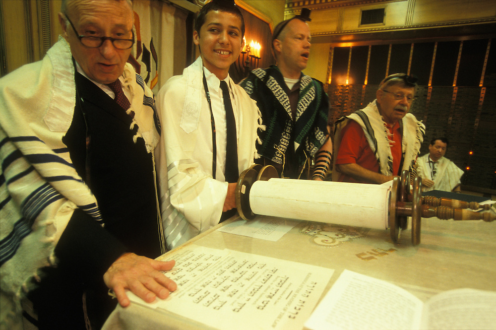 On the Monday before his bar mitzvah recital, a Jewish boy in Fair Lawn, New Jersey, USA, takes part in morning prayers at his Conservative Jewish synagogue. He also reads from the Torah, and afterwards the cantor (to his left) leads the congregation in singing a hymn. In Judaism, a boy comes of age at thirteen, when he becomes a bar mitzvah and assumes responsibility for his own actions.