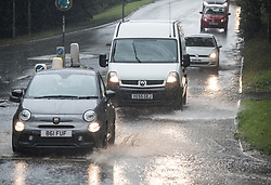 © Licensed to London News Pictures. 09/08/2017. Banstead, UK. Vehicles splash through flooding in Surrey as heavy downpours continue into the afternoon. Bands of heavy unseasonal rain are crossing the UK. Photo credit: Peter Macdiarmid/LNP
