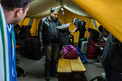 October 25, 2016 - Calais, France - A migrant reads a message from the authorities in the registration center at the jungle of Calais  in Calais, France, on 25 October 2016. Up to the evening, about 4,000 migrants from the Refugee camp on the coast at the English Channel were distributed to several regions in France. The police have begun to tear down the huts and tents in the camp. (Credit Image: © Markus Heine/NurPhoto via ZUMA Press)