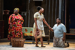 © Licensed to London News Pictures. 10/07/2012. Cape Town Opera return to the London Coliseum this July with their acclaimed production of Porgy and Bess. Picture shows: Miranda Tini (Maria), Nonhlanhla Yende (Bess) and Xolela Sixaba (Porgy). Photo credit : Tony Nandi/LNP