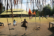 """Primary school students play on the bamboo swings overlooking the sportsfields<br /><br />The Green School (Bali) is one of a kind in Indonesia. It is a private, kindergarten to secondary International school located along the Ayung River near Ubud, Bali, Indonesia. The school buildings are of ecologically-sustainable design made primarily of bamboo, also using local grass and mud walls. There are over 600 students coming from over 40 countries with a percentage of scholarships for local Indonesian students.<br /><br />The impressive three-domed """"Heart of School Building"""" is 60 metres long and uses 2500 bamboo poles. The school also utilizes renewable building materials for some of its other needs, and almost everything, even the desks, chairs, some of the clothes and football goal posts are made of bamboo.<br /><br />The educational focus is on ecological sustainability. Subjects taught include English, mathematics and science, including ecology, the environment and sustainability, as well as the creative arts, global perspectives and environmental management. This educational establishment is unlike other international schools in Indonesia. <br /><br />Renewable energy sources, including solar power and hydroelectric vortex, provide over 50% of the energy needs of the school. The school has an organic permaculture system and prepares students to become stewards of the environment. <br /><br />The school was founded by John and Cynthia Hardy in 2008."""