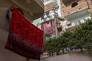 A towel airs from a line in Gezirat, a village on the West Bank of Luxor, Nile Valley, Egypt. Its bright colour showing red roses contrast with the background of more dull shades, also hanging from the homes of neighbours.