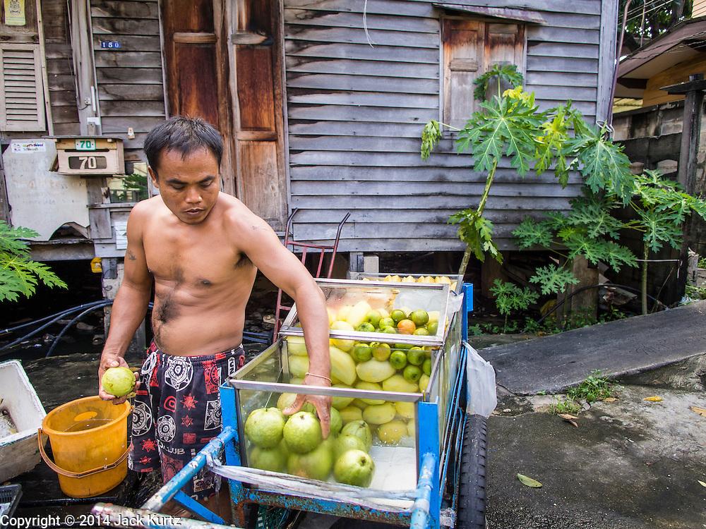 28 OCTOBER 2014 - BANGKOK, THAILAND: A vendor who sells fresh fruit from a push cart loads up his carts at the start of his day in Bangkok.   PHOTO BY JACK KURTZ