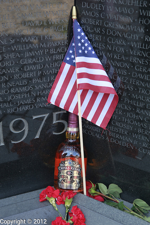 A flag and a bottle of Chivas Regal is left at the Vietnam Wall after the United States of America Vietnam War Commemoration National Announcement and Proclamation Ceremony at the Vietnam Veterans Memorial Wall.