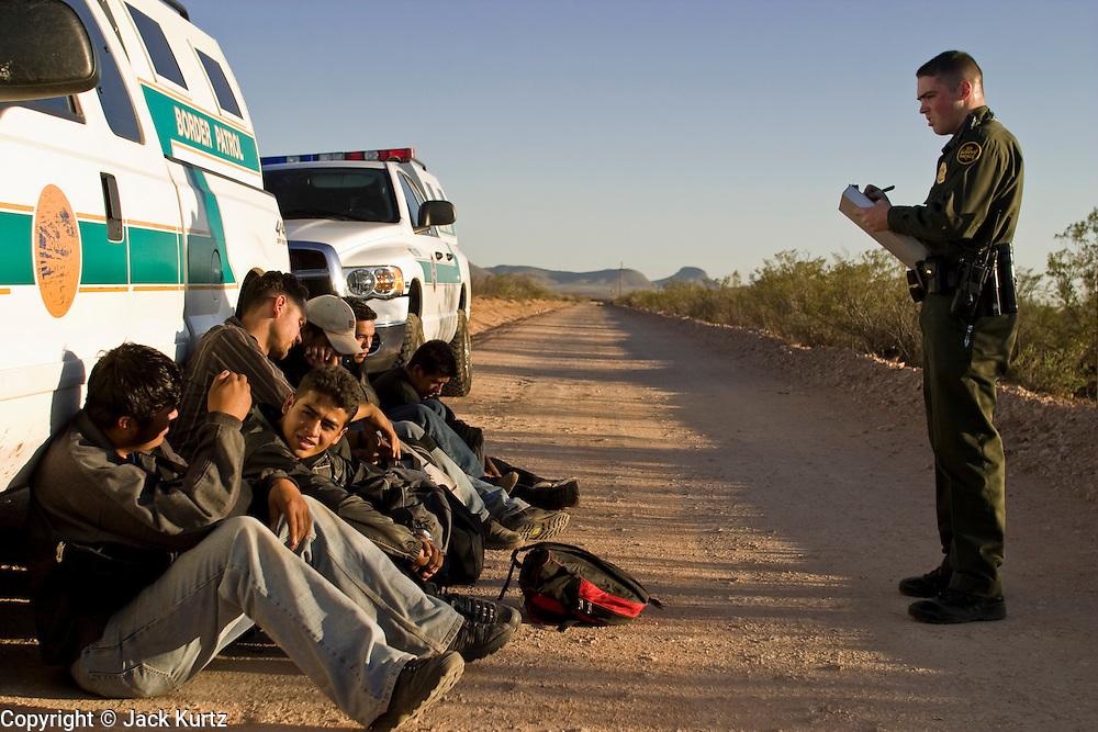 30 MARCH 2004 -- NACO, AZ: A US Border Patrol agent writes up undocumented immigrants apprehended in the San Pedro River bed near Naco, AZ. PHOTO BY JACK KURTZ