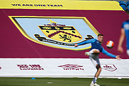 Brighton players warming up in front of a Burnley banner during the Premier League match between Burnley and Brighton and Hove Albion at Turf Moor, Burnley, England on 26 July 2020.