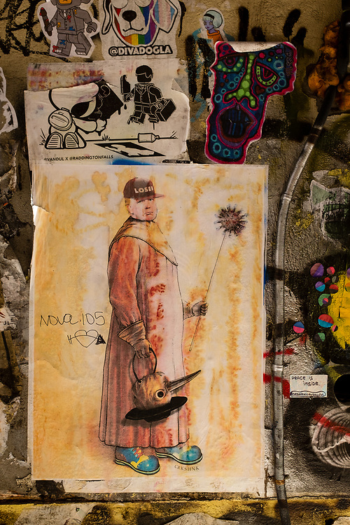 "Freeman Alley, the Bowery, New York City. Wheatpasted poster by @crkshnk of Donald Trump as a plague doctor, with a coronavirus-tipped cane (so the doctor wouldn't have to touch the patient), carrying the beaked plague-doctor's mask, and wearing a ""loser baseball cap."