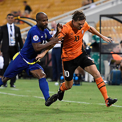BRISBANE, AUSTRALIA - JANUARY 31: Brett Holman of the Roar and Serge Kaole of Global FC compete for the ball during the second qualifying round of the Asian Champions League match between the Brisbane Roar and Global FC at Suncorp Stadium on January 31, 2017 in Brisbane, Australia. (Photo by Patrick Kearney/Brisbane Roar)