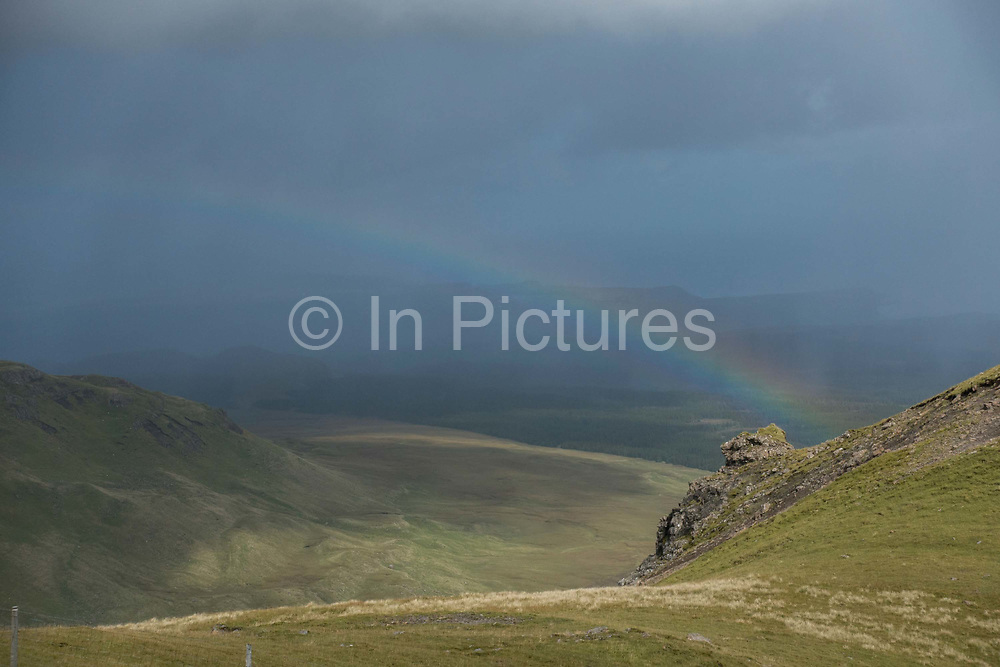 A rainbow at The Old Man of Storr on the 3rd September 2016 on the Isle Of Skye in Scotland. The 'Old Man' is a large pinnacle of rock that stands high and can be seen for miles around. Forming part of the Trotternish ridge, the Storr was created by a massive ancient landslide, and has become a popular walking and tourist destination.