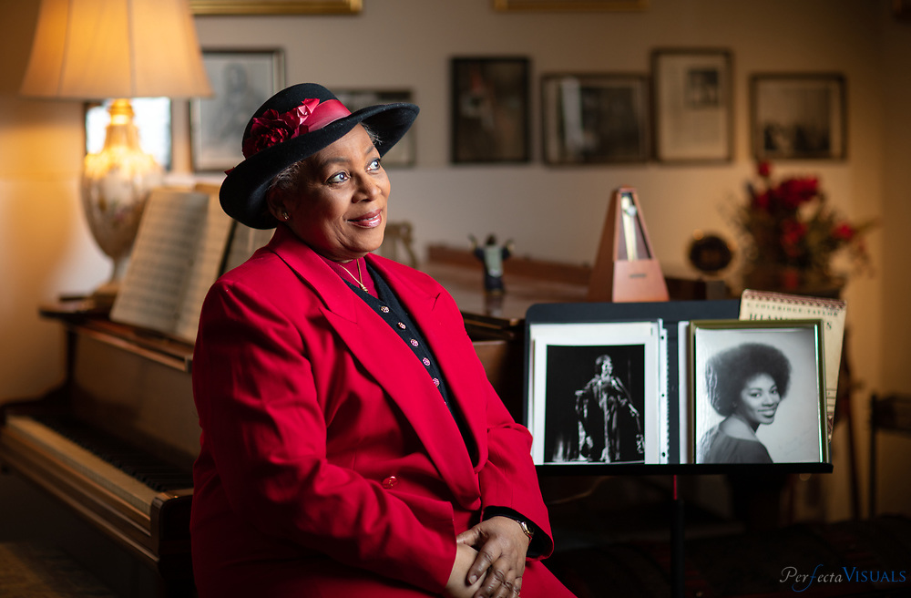 """Elvira Green beside her antique piano in her Greensboro home. Wearing one of her favorite hats  hat that is not too """"churchy.""""<br /> <br /> Elvira Green has had a prolific career as an opera singer.  She went from the Dudley High School choir to the halls of the Metropolitan Opera in New York. She was one of the few African-American women to break into a permanent spot at the Met during the 1970s as a mezzo-soprano. She performed her signature role as Maria in the opera """"Porgy and Bess."""" <br /> <br /> Photographed, Wednesday, January 16, 2019, in Greensboro, N.C. JERRY WOLFORD and SCOTT MUTHERSBAUGH / Perfecta Visuals"""