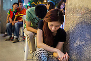24 DECEMBER 2013 - BANGKOK, THAILAND: People pray outside the church during Christmas services at Holy Redeemer Church in Bangkok. Thailand is predominantly Buddhist but Christmas is widely celebrated throughout the country. Buddhists mark the day with secular gift giving but there are about 300,000 Catholics in Thailand who celebrate religious Christmas. Catholics first came to Thailand (then Siam) in 1567 as chaplain for Portuguese mercenaries in the employ of the Siamese monarchy. There has been a continuous Catholic presence in Thailand since then.   PHOTO BY JACK KURTZ