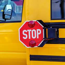 Mohnton, PA / USA - May 2, 2020: A close up view of a stop sign on a school bus in a lot in Berks County, Pennsylvania.