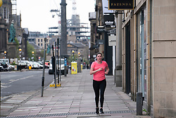 Edinburgh, Scotland, UK. 1 May 2020. Views of Edinburgh as coronavirus lockdown continues in Scotland. Streets remain deserted and shops and restaurants closed and many boarded up. Pictured; Closed shops and lone jogger on George Street.   Iain Masterton/Alamy Live News