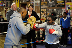 © Licensed to London News Pictures. 19/02/2013. Bristol, UK. Maria Miller (centre), the Secretary of State for Culture Media and Sport, watches Niotia Ross age 9 training in the ring with Michael Ramabeletsa, on a visit to the Empire Boxing Club in St Pauls, Bristol.  The Secretary of State is keen to build on the momentum of the Olympics and get more girls and women playing sport.  19 February 2013..Photo credit : Simon Chapman/LNP