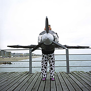 A competitor in the annual Birdman of Bognor event stands on the pier floor boards at Bognor Regis, East Sussex, England. English eccentrics gather annually at the southern seaside town to jump from the pier into the chilly waters of the English Channel. Fun jumpers 'wearing' their aeroplane suits compete for a £25,000 prize for the one to fly 100 metres from the pier platform – a record not yet achieved. Entrants (who often jump for charity rather than any aeronautical pretensions) include sugar plum fairies, condoms, Ninja Turtles and vampires. The winner was a hang-glider pilot reaching 26 metres but here, a Spitfire pilot sponsored by a milk company eventually dropped vertically. Picture from the 'Plane Pictures' project, a celebration of aviation aesthetics and flying culture, 100 years after the Wright brothers first 12 seconds/120 feet powered flight at Kitty Hawk,1903.